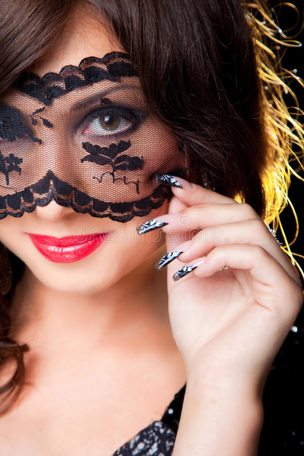 Nätt brunett med den lacy maskeringen på ögon royaltyfri fotografi