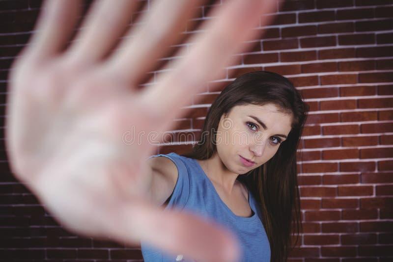 Nätt brunett med handen upp arkivfoton