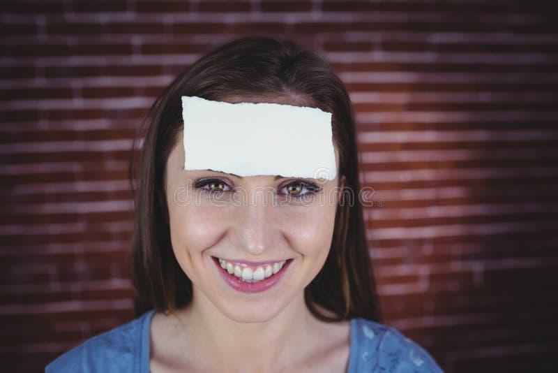 Nätt brunett med papper på huvudet fotografering för bildbyråer