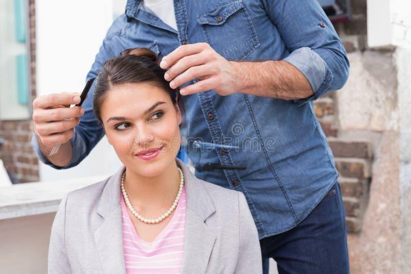 Nätt brunett som får henne hår utformat royaltyfri fotografi