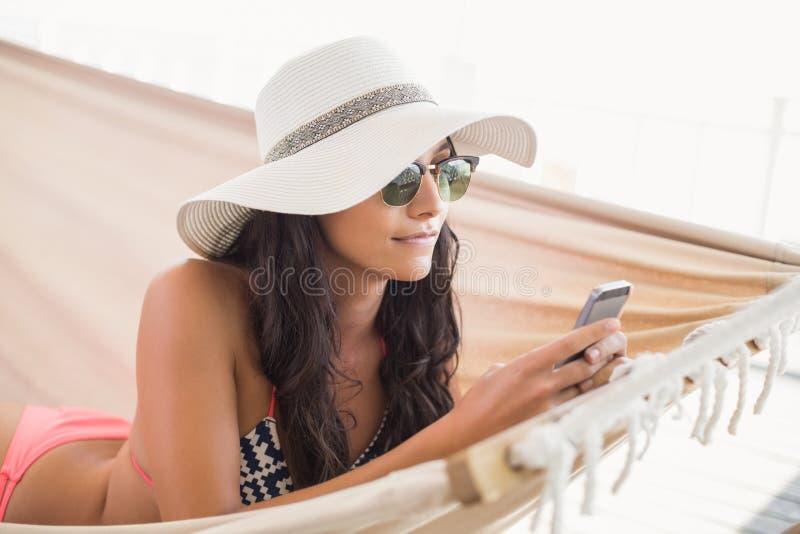 Nätt brunett som kopplar av på en hängmatta och smsar med hennes mobiltelefon royaltyfri fotografi