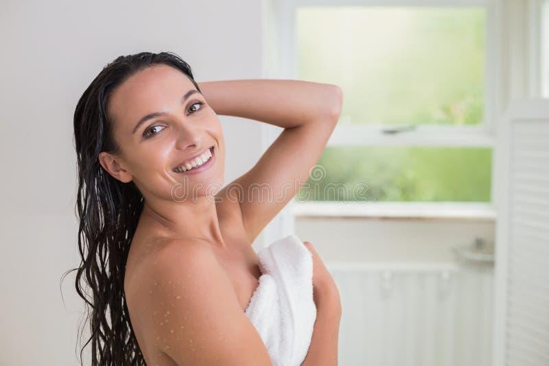 Nätt brunett som rymmer hennes badlakan arkivfoto