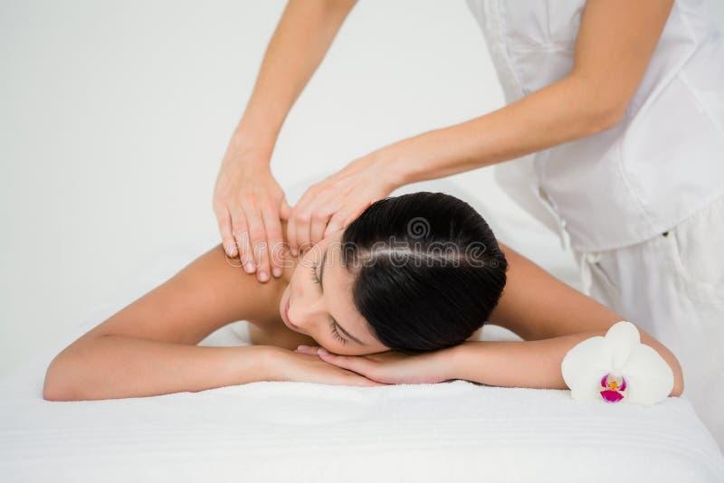 Nätt brunett som tycker om en massage med blomman royaltyfri bild