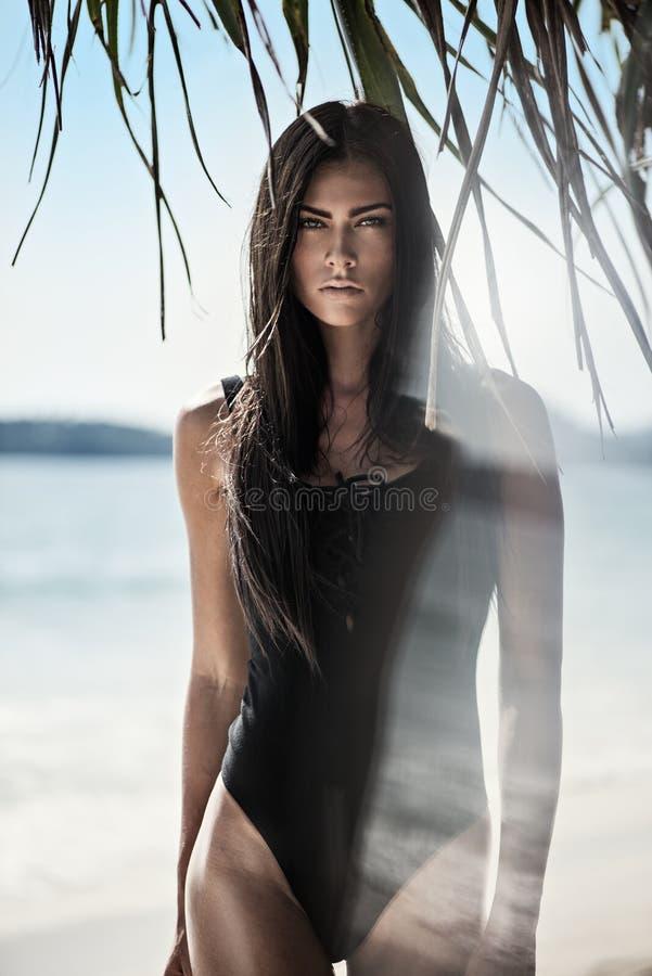 Nätt brunettdam på den tropiska stranden royaltyfri foto