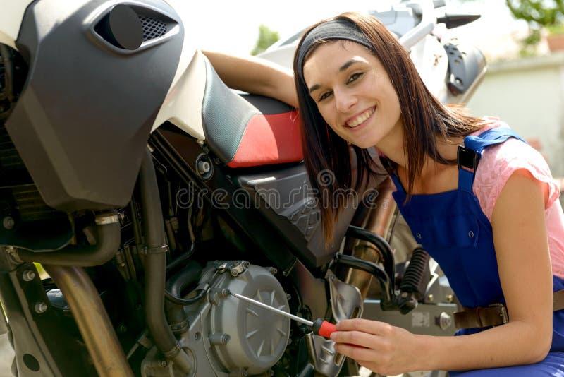 Nätt brunettflicka i mopedmekaniker royaltyfri fotografi