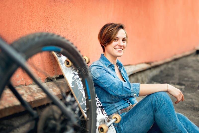 Nätt brunettflicka, skateboradåkare, moderiktigt livsstil- och hipsterflickaanseende med cykeln och longboard royaltyfria bilder