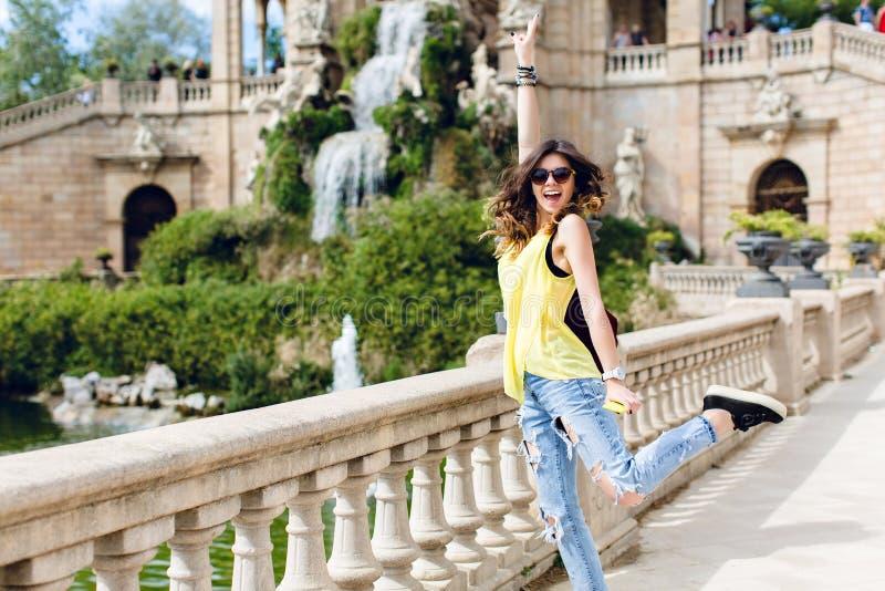 Nätt brunettflicka som har gyckel till kameran på sight- och vattenfallbakgrund Hon bär den gula T-tröja, solglasögon fotografering för bildbyråer