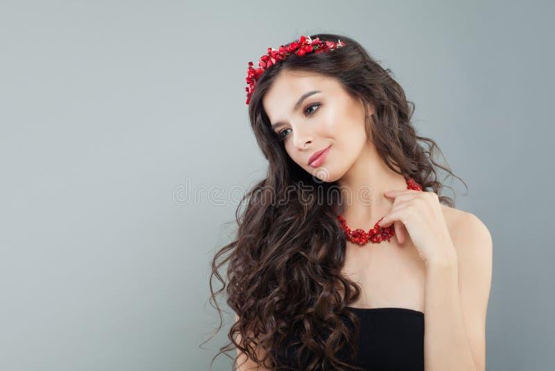 Nätt brunettkvinna med makeup, långt lockigt hår och halsbandet för röd korall på grå bakgrund fotografering för bildbyråer