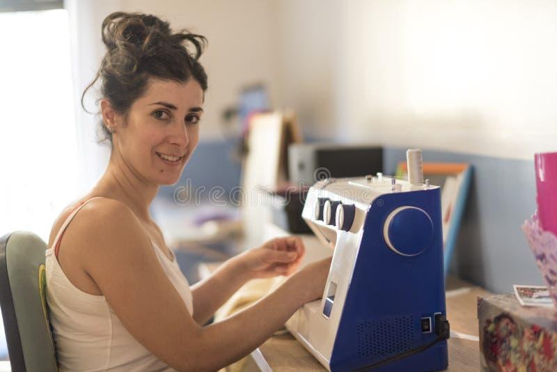 Nätt brunettkvinna som hemma syr i maskin royaltyfria foton