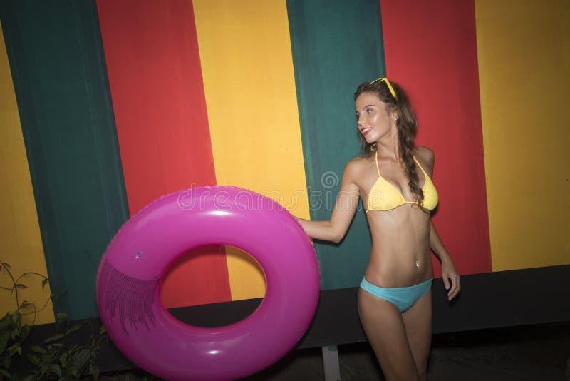 Nätt cirkel för bikini för ung kvinna bärande hållande rosa uppblåsbar på den färgglade väggen royaltyfri foto