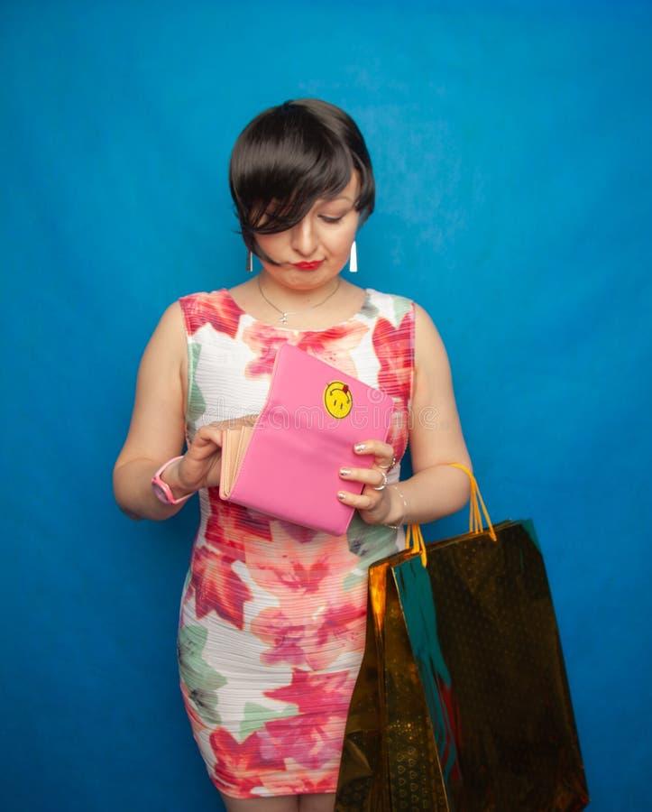 Nätt curvy kvinna i den vita åtsittande klänningen som öppnar hennes rosa tomma plånbok och mycket ledset därför att inga pengar  royaltyfria bilder