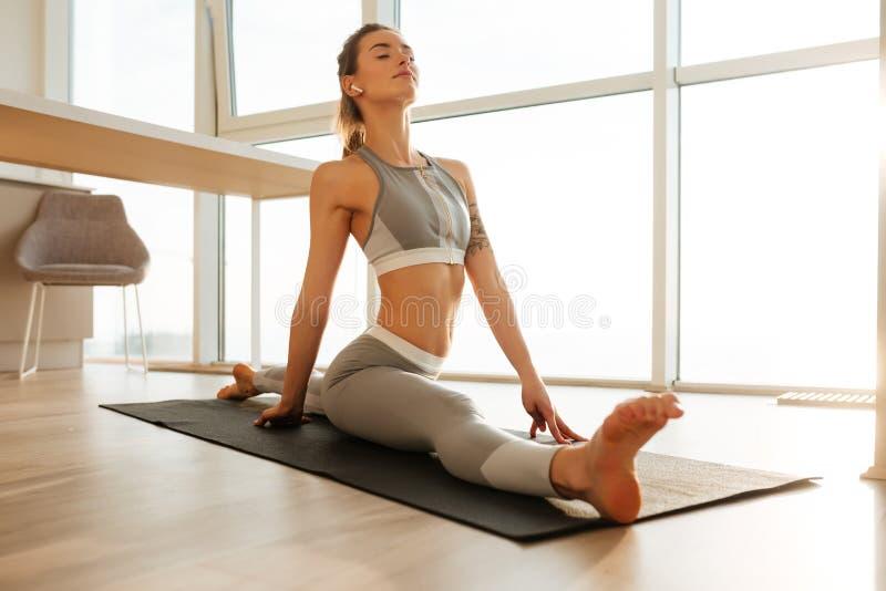 Nätt dam i sportig överkant och damasker som hemma öva kondition på matt lyssnande musik för yoga royaltyfri bild