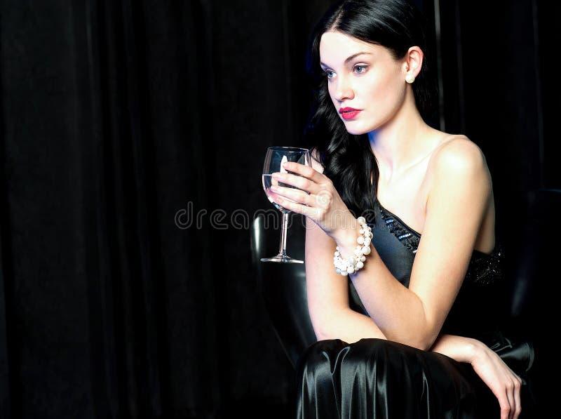 Nätt dam som är borttappad i hennes värld, hållande vinexponeringsglas royaltyfria foton