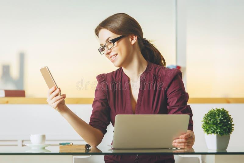 Nätt dam som använder smartphonen och bärbara datorn arkivfoton