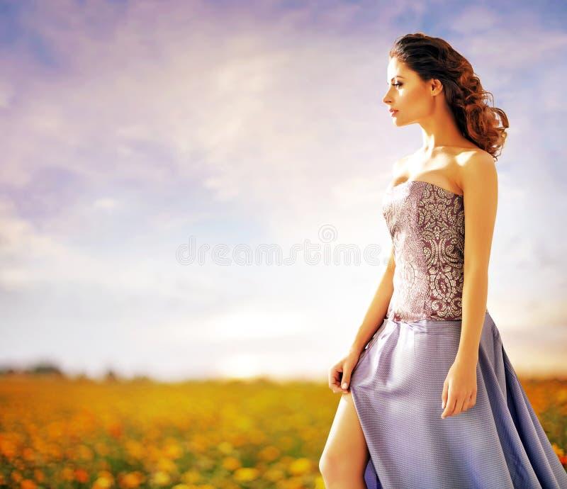 Nätt dam som går på sommarfältet royaltyfria bilder