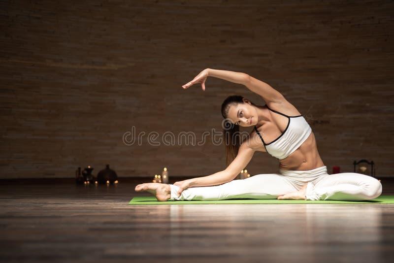 Nätt dam som ser dig, medan sträcka under yogagruppen royaltyfri fotografi