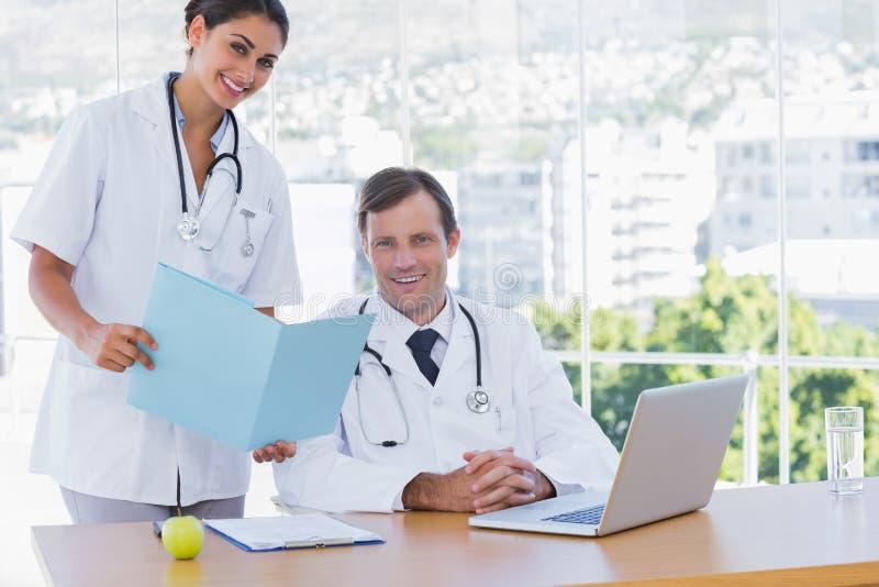 Nätt doktor som visar en mapp till en kollega fotografering för bildbyråer