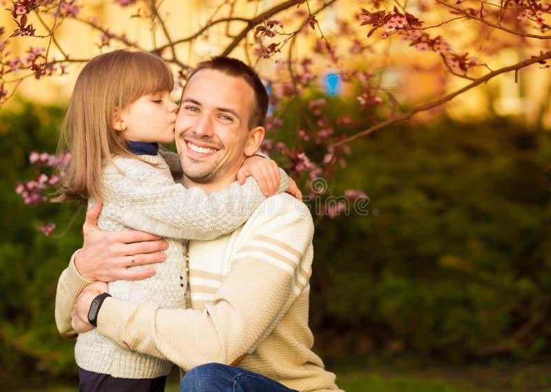 N?tt dotter f?r n?ra ?vre st?ende som omfamnar den Caucasian fadern Familjen tycker om f?r att spendera tid tillsammans royaltyfri fotografi