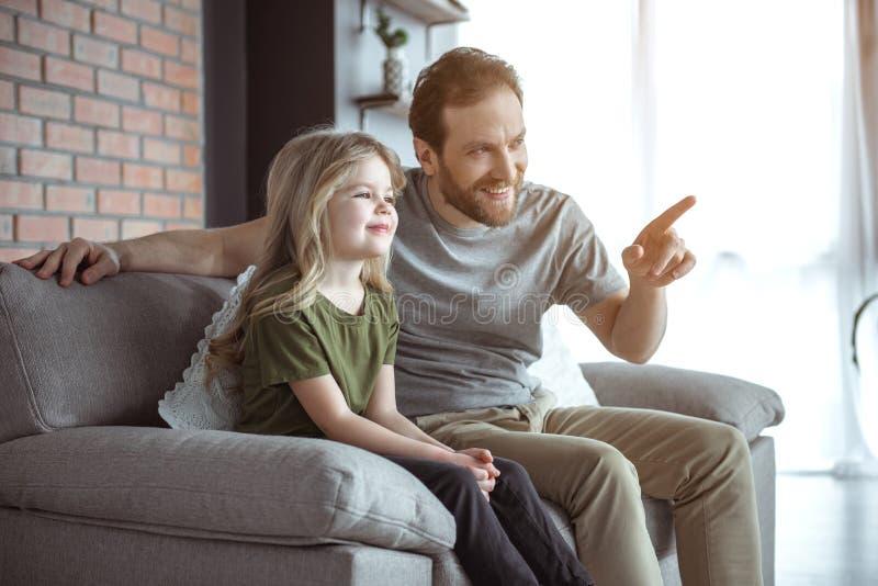 Nätt dotter som lyssnar för att avla uppmärksamt i hem royaltyfri fotografi