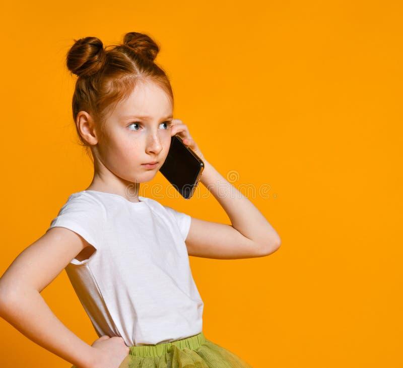 Nätt emotionell liten flicka som talar vid mobiltelefonen royaltyfria foton