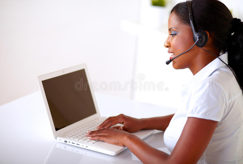 Nätt etnisk kvinna som fungerar på kundtjänst arkivfoto