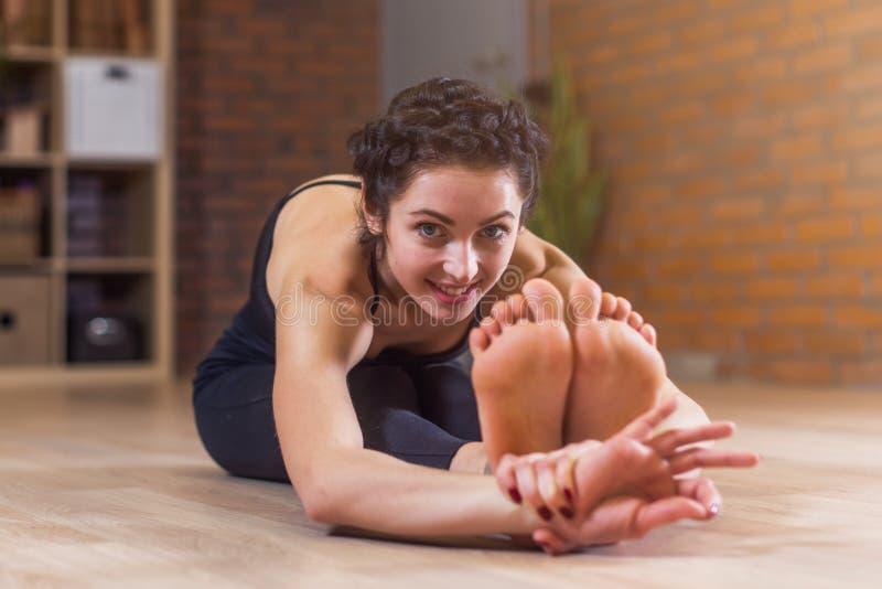 Nätt europeisk kvinna som sitter barfota sträcka henne tillbaka och ben på golvet som böjer framåt kameran för se arkivbild