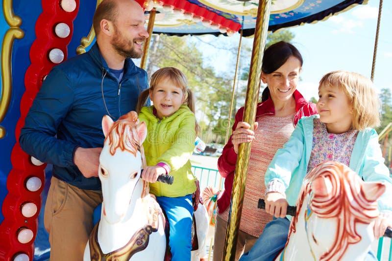 Nätt familj som har gyckel på karusell arkivbild