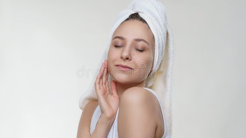 Nätt fantastisk kvinna med perfekt ren hud i en handdukmjukhet som poserar med lyckligt leende på vit bakgrund royaltyfria bilder
