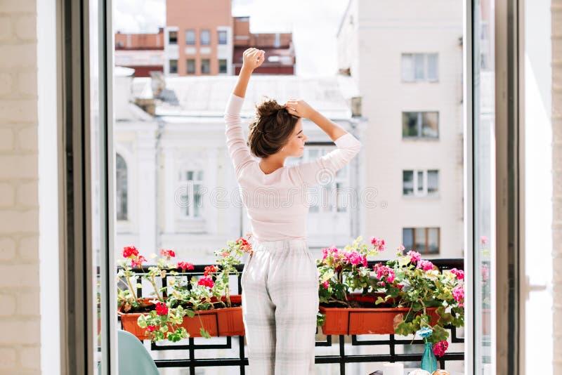 Nätt flicka från baksida i pyjamas på balkong i solig morgon Hon lyfter handen över, blickar tyckte om med stängda ögon royaltyfri bild