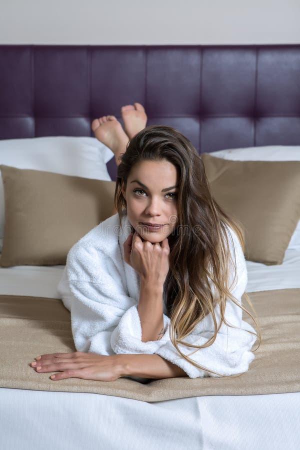 Nätt flicka i badrock på säng arkivfoton
