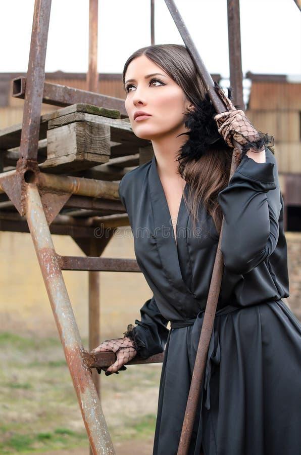Nätt flicka i elegant svart klänninganseende på materialet till byggnadsställning royaltyfria foton