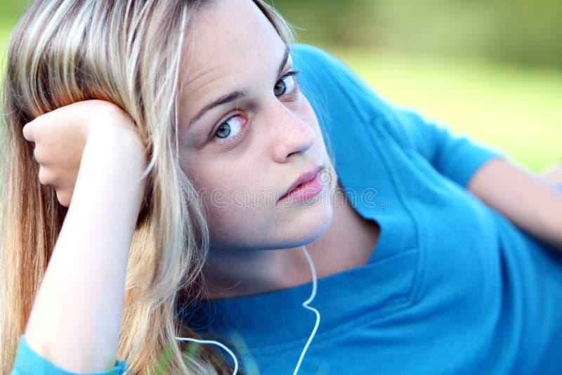 Nätt flicka i fjäder med musik arkivbild