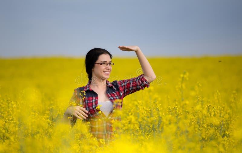 Nätt flicka i gult rapsfröfält arkivfoto