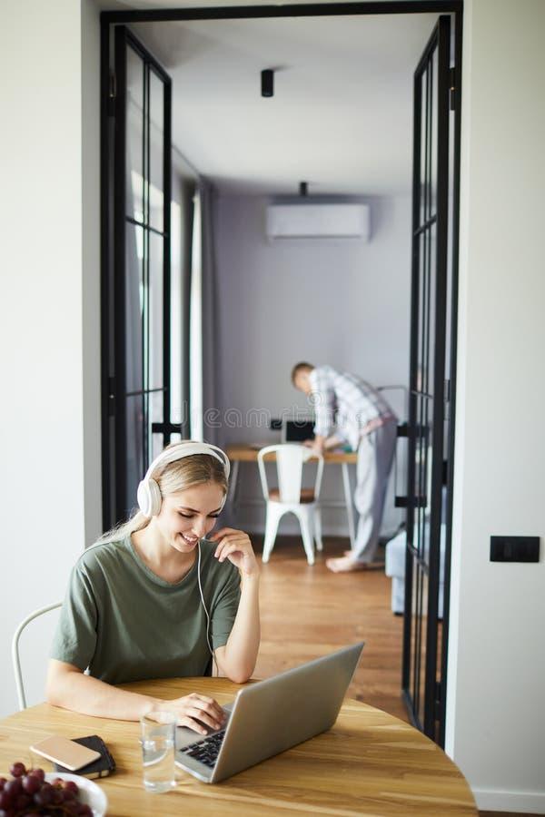 Nätt flicka i hörlurar som ser bärbar datorskärm under nätverk royaltyfri bild