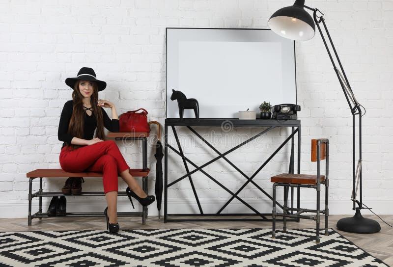 Nätt flicka i hattsammanträde på en bänk i studion fotografering för bildbyråer