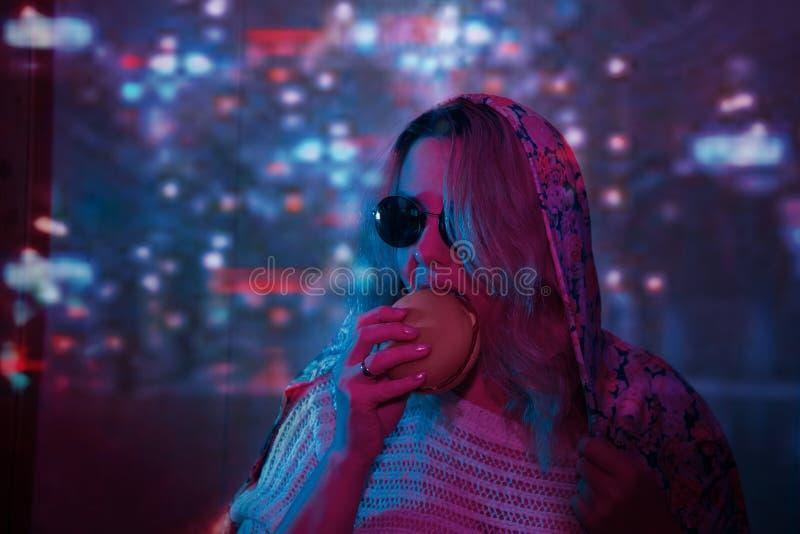 Nätt flicka i stilfulla exponeringsglas Stil moderna för nattstad för neon ljusa ljus arkivfoton