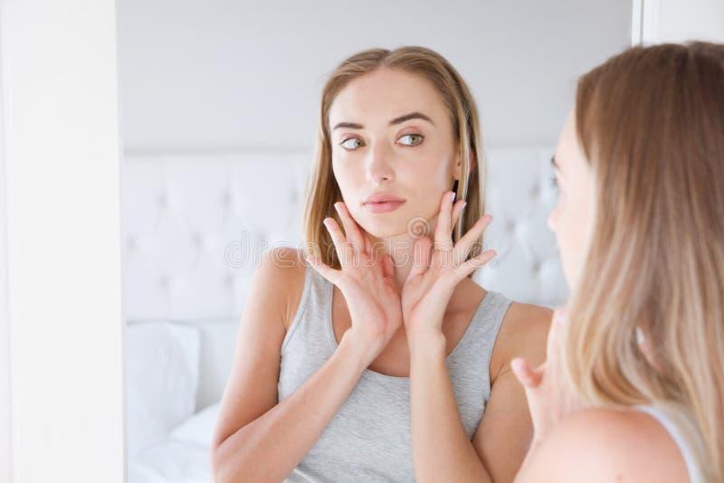 Nätt flicka, kvinna som trycker på hennes hals, medan se i spegeln, skönhetbegrepp royaltyfri bild