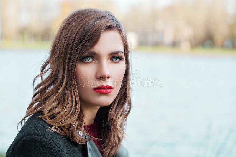 Nätt flicka med den sunda lockiga bruna frisyren arkivbilder