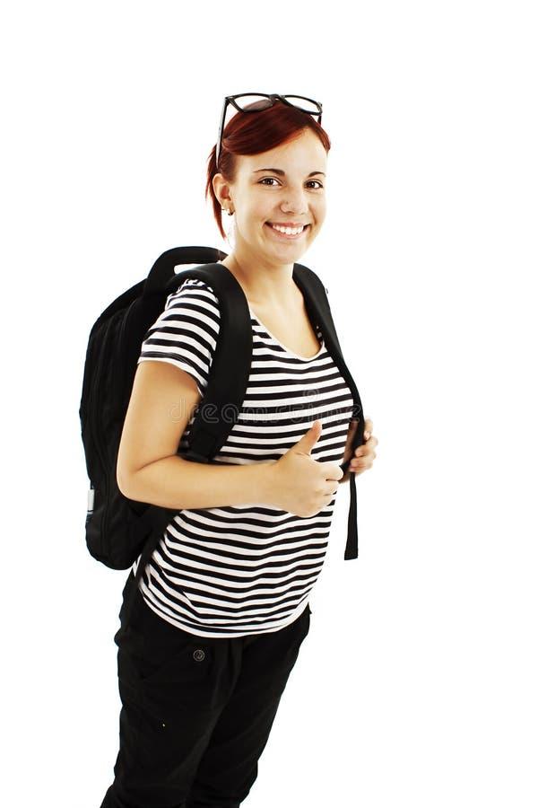 Nätt flicka med ryggsäcken som visar henne thumb-up. royaltyfri bild