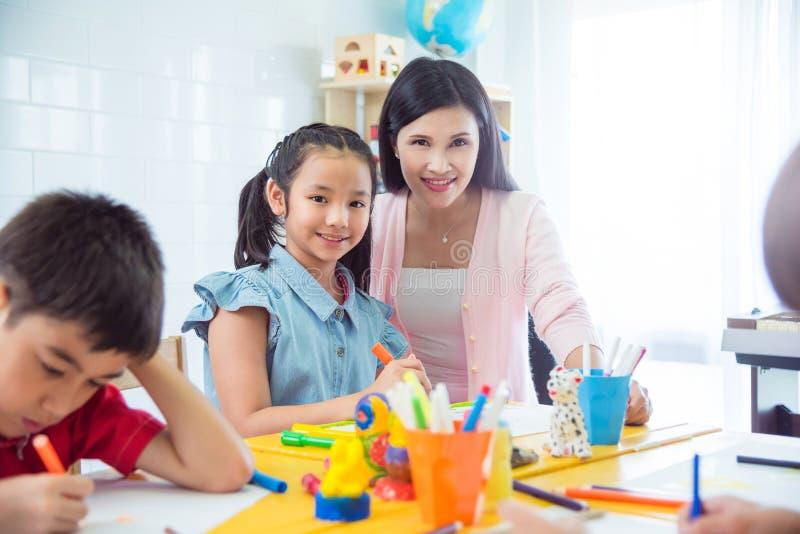 Nätt flicka och lärare som ler i klassrum arkivbild