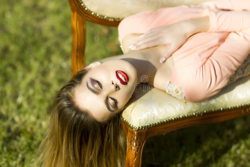 Nätt flicka på den utomhus- soffan royaltyfri bild