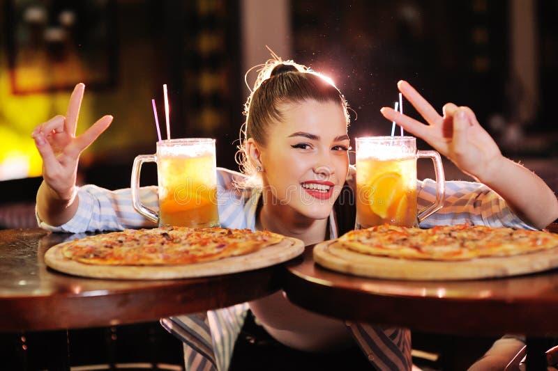 nätt flicka som äter pizza och dricker öl eller en citrus coctail för öl på bakgrunden av en stång eller pizzeria arkivbild