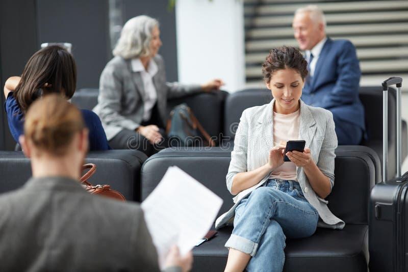 Nätt flicka som använder apparaten i flygplats royaltyfri foto