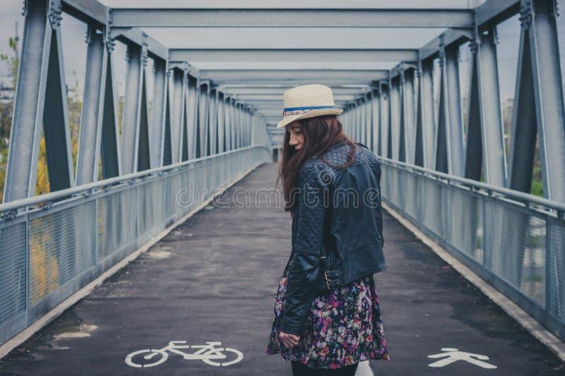 Nätt flicka som bort går på en bro royaltyfria foton
