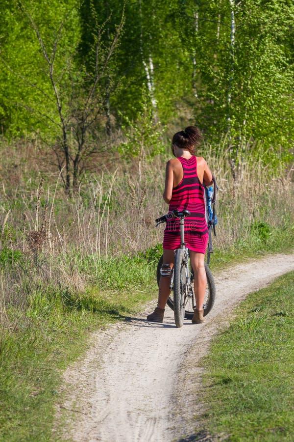 Nätt flicka som cyklar i den lösa naturen på grusvägen Cyklar som cyklar flickan Flickarittcykel royaltyfri foto