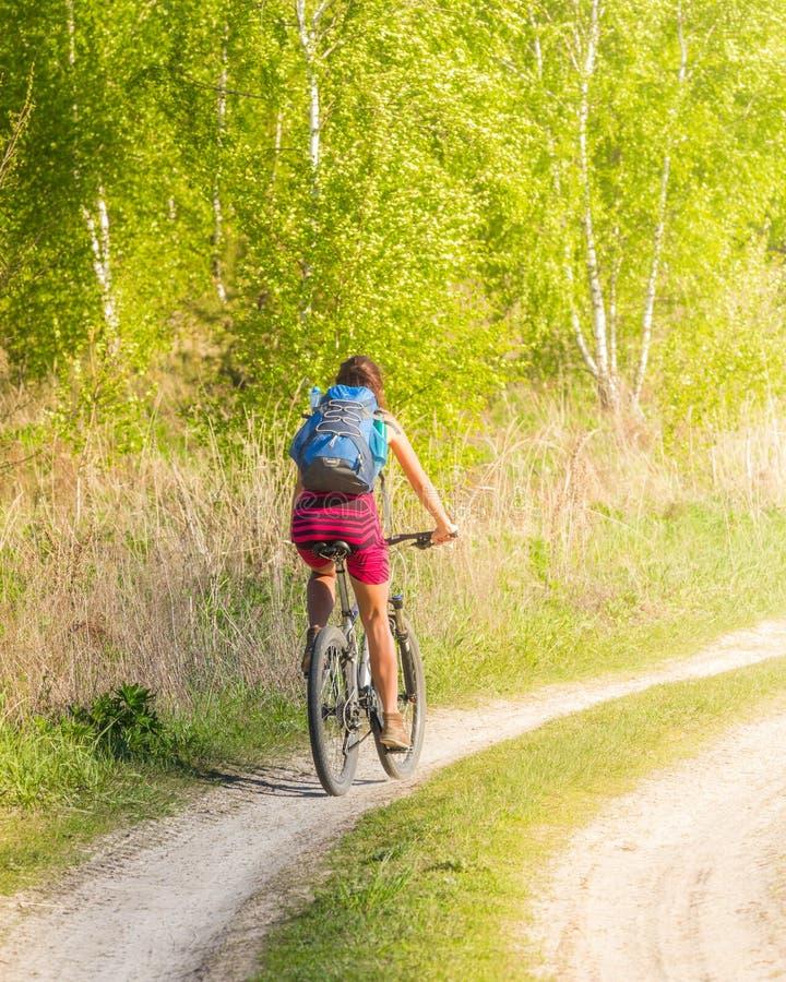 Nätt flicka som cyklar i den lösa naturen på grusvägen Cyklar som cyklar flickan Flickarittcykel arkivfoto