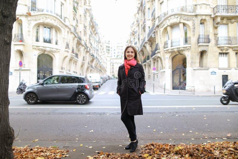 Nätt flicka som går i höststad på gatan med bilar och byggande bakgrund royaltyfri foto
