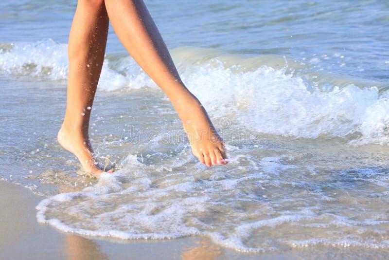Nätt flicka som går i vatten arkivbild