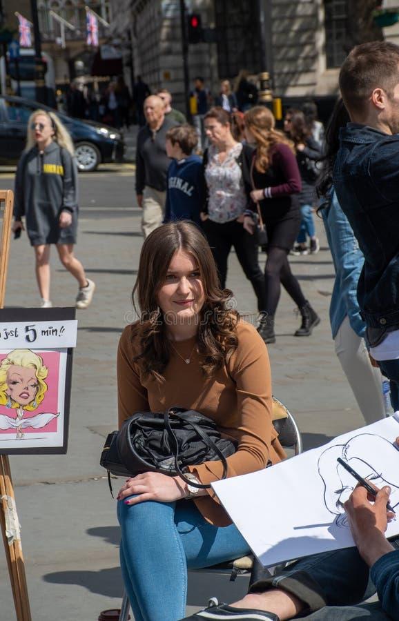 Nätt flicka som har karikatyr att dras av gatakonstnären arkivbilder