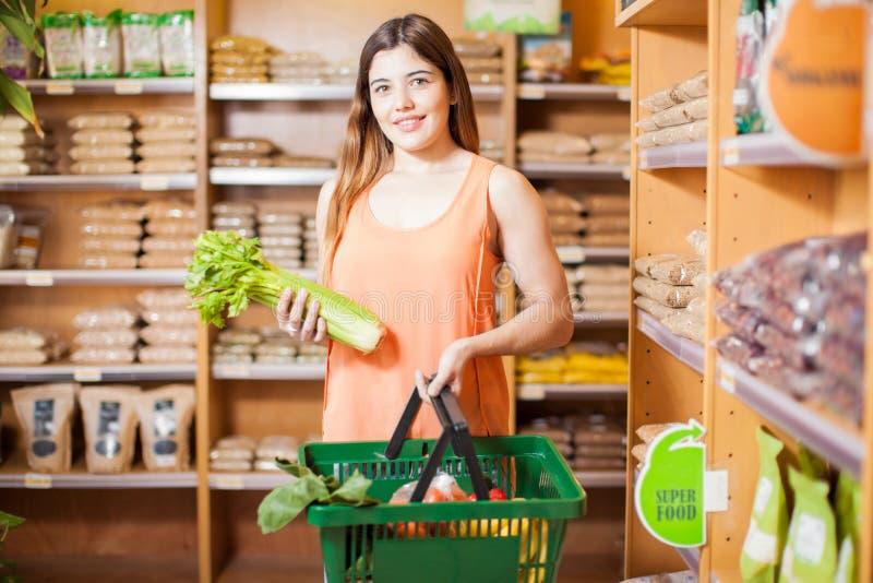 Nätt flicka som köper sund mat på ett lager arkivfoto